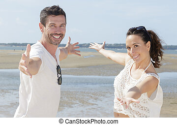 happy couple with open arms on the beach