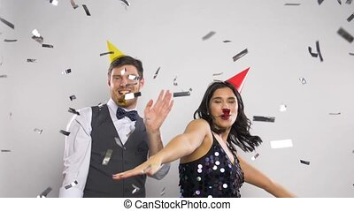 happy couple with party blowers having fun - celebration,...
