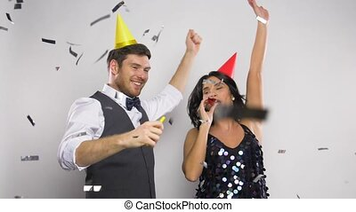 happy couple with party blowers having fun