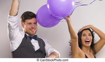 happy couple with purple balloons dancing at party -...