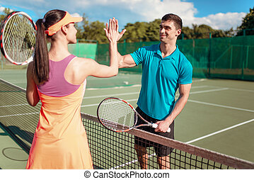 Happy couple with rackets on outdoor tennis court