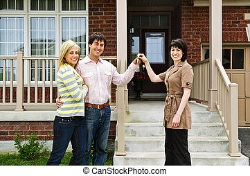 Happy couple with real estate agent - Happy couple getting ...