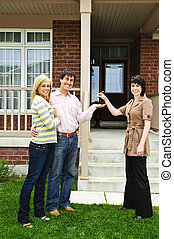 Happy couple with real estate agent - Happy couple getting...