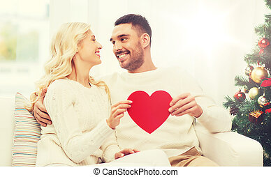 happy couple with red heart at home for christmas - family,...