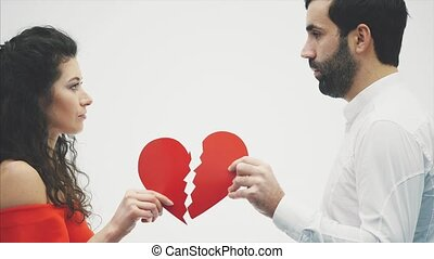 Happy couple with red heart origami. Valentine's Day. Love each other. Good holidays. The concept of celebration of love. Young and beautiful people. The feeling of the show. Funny lovers.