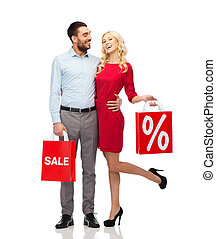 happy couple with red shopping bags - people, sale, discount...