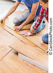 happy couple with ruler measuring parquet board - repair,...