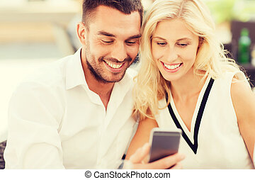 happy couple with smartphone at city street cafe
