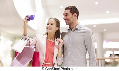 happy couple with smartphone taking selfie in mall