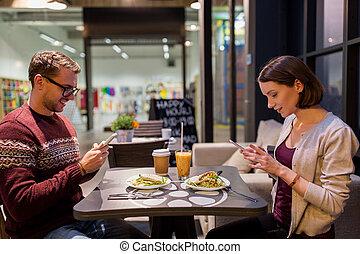 happy couple with smartphones at vegan restaurant -...