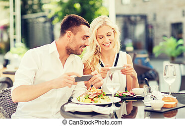 happy couple with smatphone photographing food - love, date...