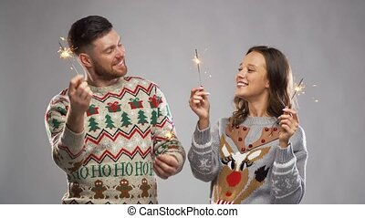 happy couple with sparklers at christmas party -...
