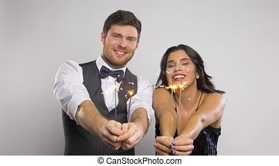 happy couple with sparklers at party - celebration, fun and...