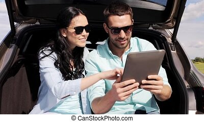 happy couple with tablet pc at hatchback car trunk