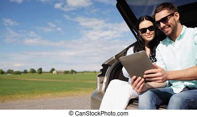 happy couple with tablet pc at hatchback car trunk 33