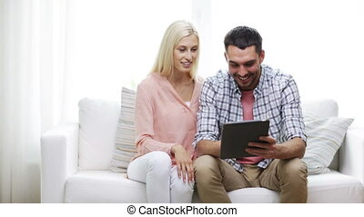 happy couple with tablet pc at home