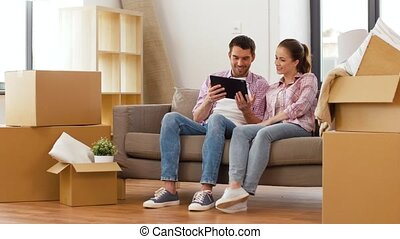 happy couple with tablet pc computer at new home - mortgage,...