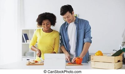 happy couple with tablet pc cooking food at home - cooking,...