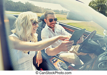 happy couple with tablet pc in cabriolet car