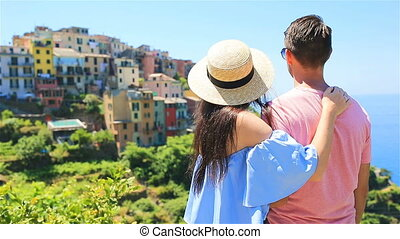 Happy couple with view of the old coastal village background of Corniglia, Cinque Terre national park, Liguria, Italy ,Europe