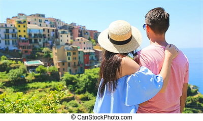 Happy couple with view of the old coastal village in Italy