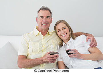 Happy couple with wine glasses sitting on sofa