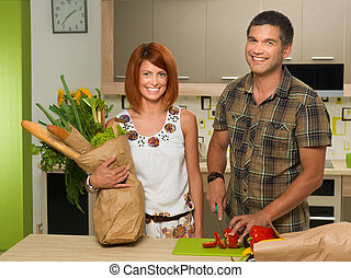 happy couplestanding in kitchen and cooking