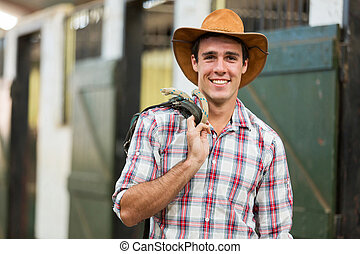 cowboy carrying reins of a horse - happy cowboy carrying...