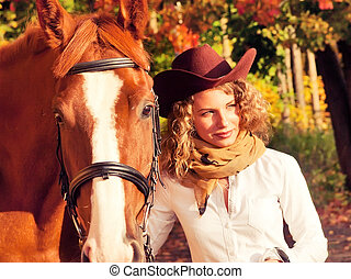 Happy cowgirl with her red horse.
