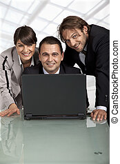 happy coworkers behind a laptop