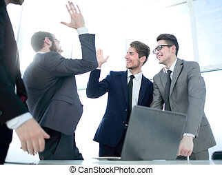 happy coworkers giving each other a high five. concept of ...