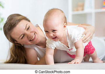 Happy crawling baby girl with mother