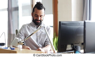 happy creative male office worker with computer