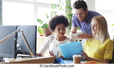 happy creative team with computers in office - business,...