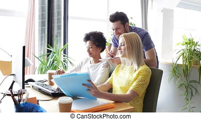 happy creative team with computers in office