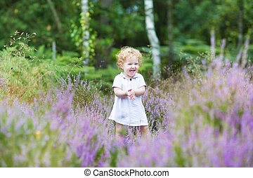 Happy curly baby girl laughing and playing in a heathland with b