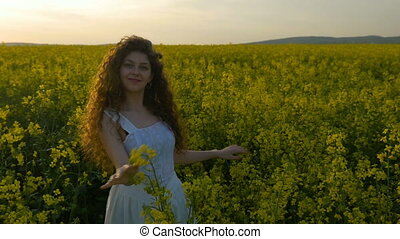 Happy curly girl dancing in rapeseed field enjoying summer at sunset
