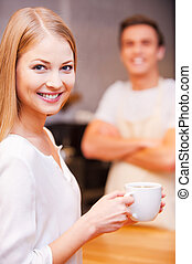 Happy customer. Beautiful young woman holding cup of coffee and smiling while standing near bar counter and with cheerful barista standing in the background