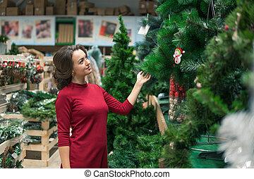 happy customer girl choosing Christmas tree for the new year...