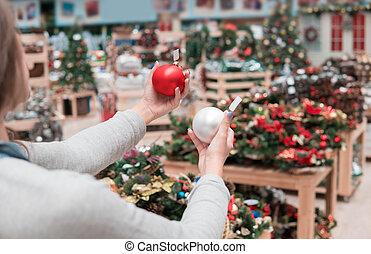 happy customer girl choosing Christmas tree decoration...