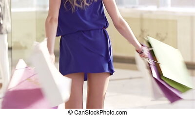 Happy young woman carrying purchases and turning around in slow motion