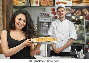 Happy customer keeping pizza in hands and posing in cafe