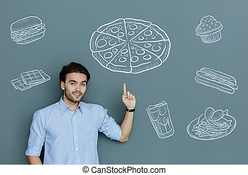 Happy customer ordering a big pizza and pointing at it