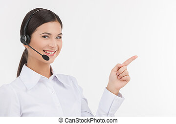 Happy customer service representative. Beautiful young female customer service representative in headset pointing away and looking at camera while isolated on white