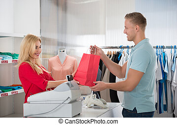 Happy Customer Taking Shopping Bag From Saleswoman In Store