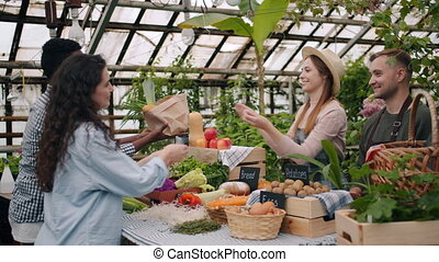 Happy customers taking paper bag with organic food and giving money to farmers
