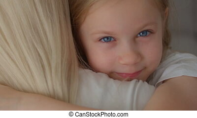 Happy cute affectionate adopted little kid girl hugging foster care parent mother with blue eyes, adorable small child daughter embrace mum cuddling enjoy tender sweet moment concept