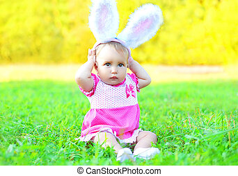 Happy cute baby with rabbit ears on grass in sunny spring day