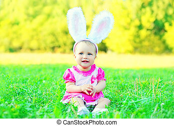 Happy cute baby with rabbit ears on grass in sunny summer day