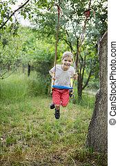 Happy cute boy on swing in garden